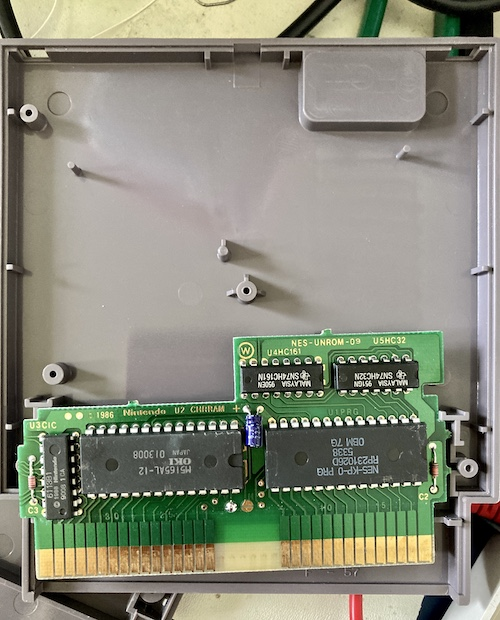 The inside of a Casino Kid cartridge. The main PCB is NES-UNROM-09, and it is equipped with an OKI M5165AL-12 RAM chip for character RAM, a Nintendo-branded CIC chip, an NES-KP-0 mask PRG ROM, a 74HC32 OR-gate, and a 74HC161 binary counter.