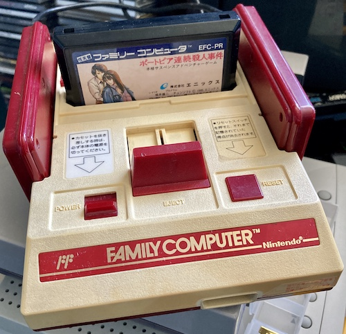 The Famicom, reassembled and with a copy of Portopia in the cartridge slot. It's sitting on top of a Bandai Pippin (spoiler alert.)