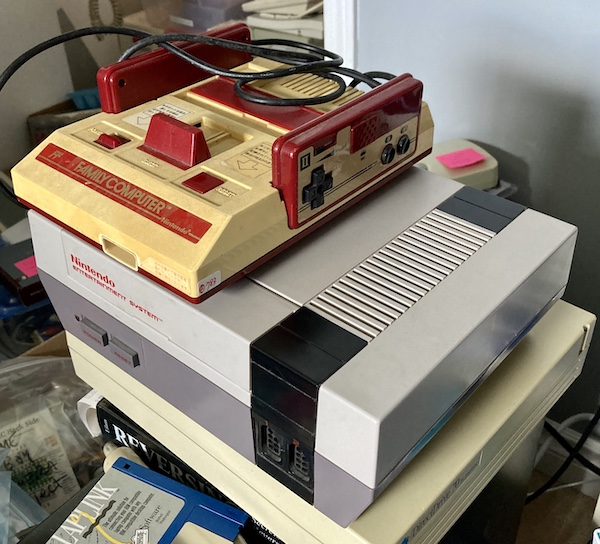 A Famicom is sitting on top of an American front-loading NES, which is a spoiled Western brat and doesn't like loading cartridges.