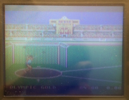The Game Gear is displaying a little Caucasian pixel man trying to chuck a shot-put in an imagined version of a future Olympics that had happened decades prior to this shot being taken.