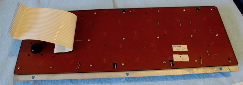 Backside of the keyboard PCB. There are stickers reading MITSUMI 841102 and 46442511