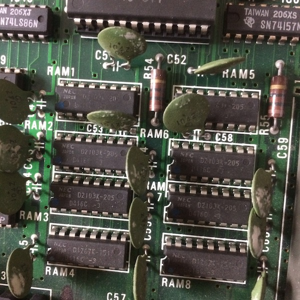 The PC-6001's RAM. There are eight of them, numbered from RAM1 to RAM8. They are NEC 416C parts. Each one seems to have a weird green ceramic disc capacitor for filtering.