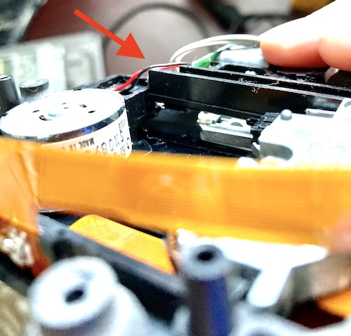 I am holding the disc-drive assembly upside down. There is a red arrow pointing to the piece of plastic that is jutting out at an awkward angle.
